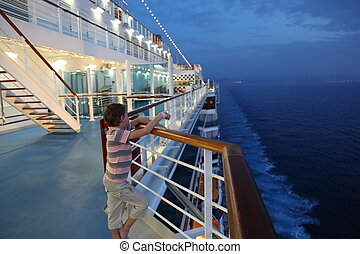 little boy wearing shorts and striped shirt standing on deck...
