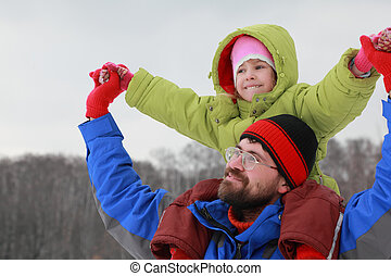 Father holds daughter on shoulders and glad