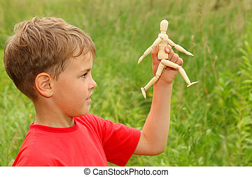 boy in red T-shirt is played by wooden little manikin in...