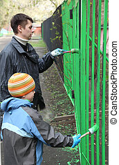 Little boy and his father stand back and dye fence by green...