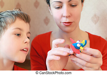 Mother and  son play with  home-made elephant from plasticine