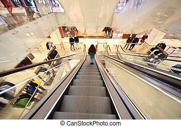 Girl goes down on an escalator in  shopping center