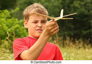 little boy in red T-shirt plays with wooden airplane on nature