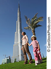 DUBAI - APRIL 17: Mother with child in front of Burj Khalifa (Burj Dubai) , 17 april 2010 in Dubai, UAE. Emirat Dubai - the main tourist zone in the Near East.