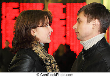 Profile of man and woman in leather jacket look to each other in eye on background of flight timetable