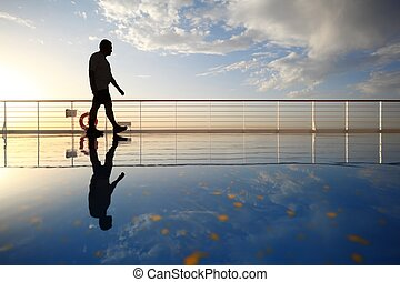 silhouette of old man walking throught deck of cruise ship. morning golden sun shining. reflection in deck.