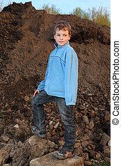 Little boy in blue jacket stands on earthen embankment at...