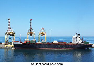 big merchant ship with cargos on a board at its moorings in...