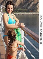 beautiful woman with her daughter both wearing swimming suit are standing on deck of cruise ship