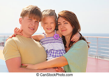 happy family with daughter on cruise liner deck, mother and father carrying their daughter on hands, half body