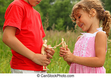 little brother and sister play with wooden little manikins in nature. manikins greet each other. focus on manikins.