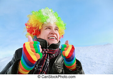 Man in wig and gloves of clown looks in sky and shows gestures hands