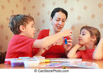Mother and two children are at  table and model from plasticine, home-made elephant