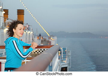 smiling beautiful woman wearing swimming suit is standing on deck of cruised ship and looking away