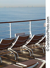 many chaise longues on deck of cruise ship in out of focus....