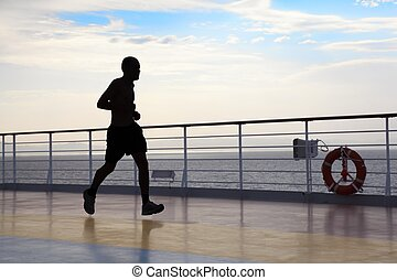 silhouette of man wearing shorts is running on deck of cruised ship.