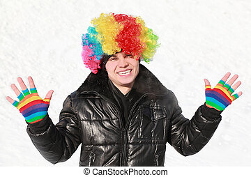Boy stands in wig of clown and shows bright gloves
