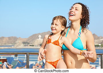smiling beautiful woman with her daughter is standing on...
