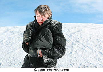 Fellow stands in winter on snow holds  brief-case and shows gesture fingers
