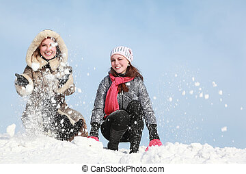 Two young women squatting and throw snow