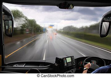front window of bus and rainy road