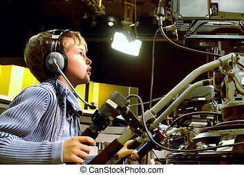 Little boy with headphones and microphone looks to...