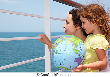 mother and daughter on cruise liner deck, child holding inflatable globe, half body