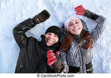 Two lovers people lie on in winter on snow  holding  hands and smile