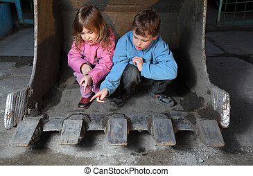 Little girl in pink clothes and boy in blue jacket sitting inside bucket of crawler tractor