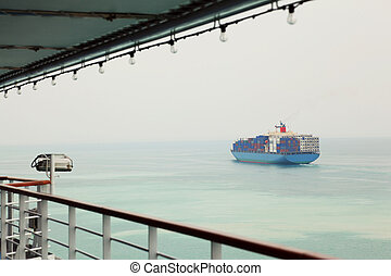 cargo tanker with containers in sea, view from other ship