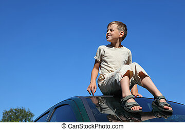 Boy sits on roof of car and looks aside