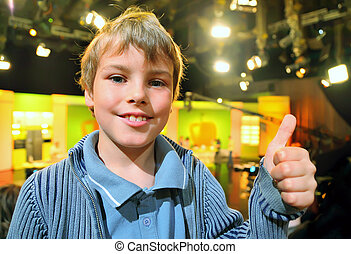 """Little smiling boy stands in auditorium and shows """"ok"""" against the background of television broadcast"""