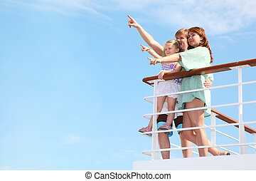 young happy family rests on yacht and indicates something...