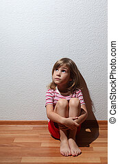 Little girl in casual clothes looks sad to corner, whence...