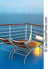 Two illuminated deck-chair on ship deck overlooking city...