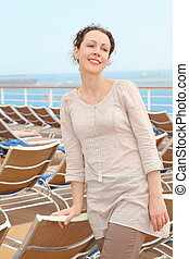 beautiful woman standing on deck of cruise ship near chaise longue.