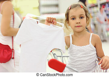 little girl sitting in store cart and holding hanger with...