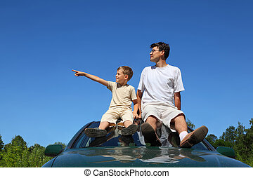 Father with son of sit on roof of car in day-time and look...