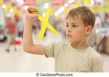little caucasian boy holding yellow boomerang toy, standing in big store, looking at side