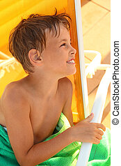 Cheerful little boy sits in yellow deck chair and wrap...