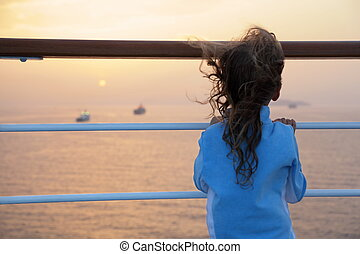 little girl wearing tracksuits is standing on deck of ship and looking at setting sun. ship in out of focus.
