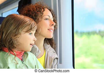 Mother with daughter ride in speed train on rest in day-time...