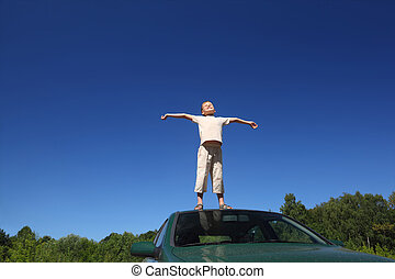 Boy stands on  head of auto, lifts  face in sky and sends hands in sides