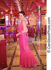 beautiful smiling woman wearing evening dress standing in illuminated hall.