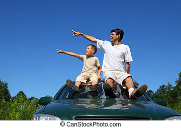 Father with son sit on roof of car in day-time and look...