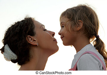 portrait of mother and daughter looking to each other, side view, outdoor