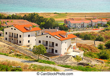 Construction of new two-storey white houses with brown roofs...