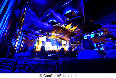 Old people watching concert in the dark room on the cruise ship