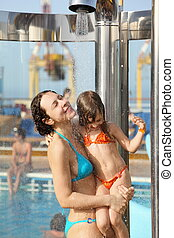beautiful woman with her daughter both wearing swimming suit are taking a shower on deck of cruise ship.