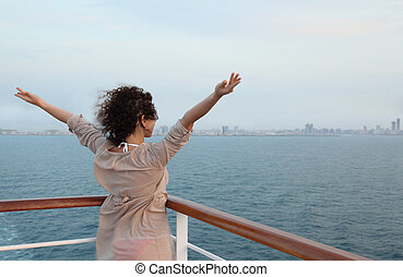 Wind in girl face. She standing on deck and watching the city at evening
